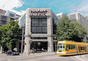 View of the front of the Streetcar Lofts building with a yellow streetcar passing in front.