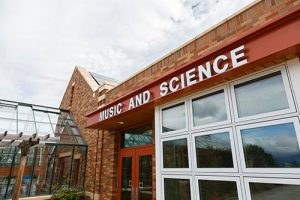 Front of a school building. Sign says Music and Science.
