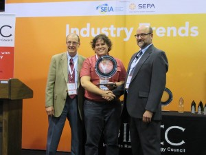 three people one receiving a solar energy award