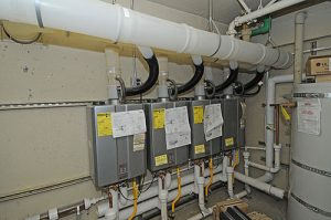 Three tankless water heaters in a multifamily property basement.