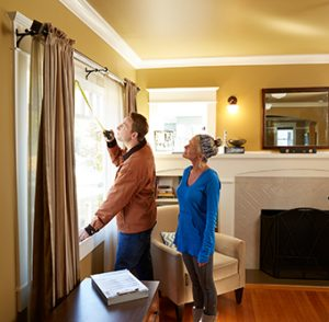 Man measuring windows with a tape measure in a home with a woman watching him.