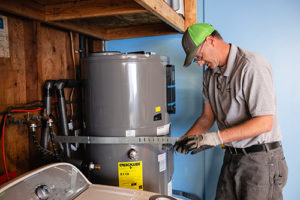 A Community Energy Project worker strapping down a water heater.