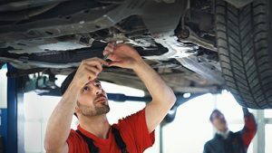 Mechanic working with tools under a raised-up car.