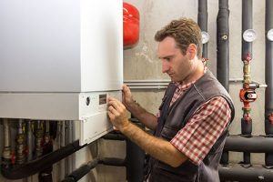 Man adjusting the controls on a commercial boiler.
