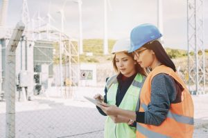 Two young electrical female engineers with hard hats standingwith digital tablets in front of electrical components and wind turbines.