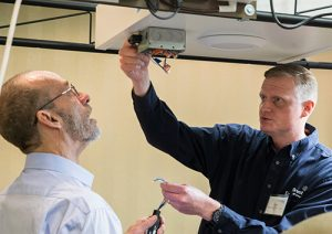 Two men looking at electric wiring on the ceiling.
