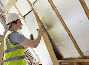 A man in a white hard hat installing insulation in a roof.