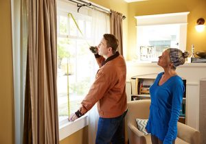 Woman watching a contractor measure a window in her home.