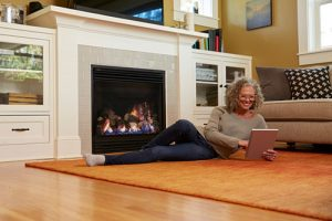 Lady looking at her tablet in front of a fireplace