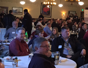 Attendees at a trade ally forum sitting at tables listening to presentations