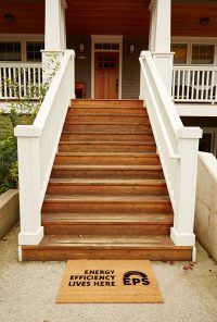 Stairs leading up to a house. Wooden steps and white railings.