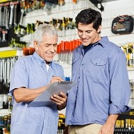 two men looking at a clip board with a wall of tools in the background