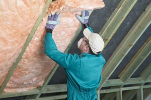 A man with a white hat and mask putting up insulation in a ceiling.
