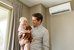 father and child in house with wall mounted temperature control unit