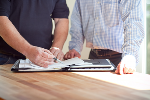 a close up of two mens torsos and arms going over paper work on a wood table