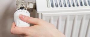 Person adjusting temperature on heater