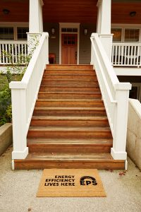 entry way of home with door mat reading energy efficiency lives here