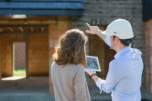 View of a woman and architect on construction site pointing at a house.