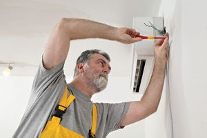 repairman working on a wall mounted temperature control unit