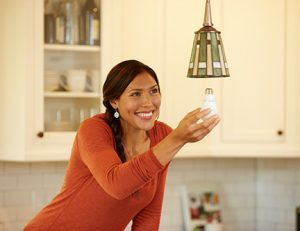 a women changing a light bulb in her kitchen