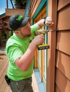Man in green shirt and black and green hat using a drill on the side of a house.
