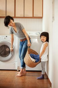 Woman and her daughter holding laundry basket in front of a front-loading clothes washer.