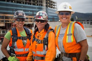 Three women workers in hardhats and orange vests