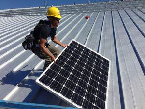 Solar installer on roof placing a solar panel.
