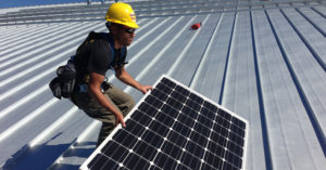 A man installing solar panels on a metal roof