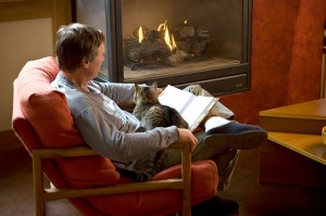 a man in a chair with a cat in his lap reading by the fire