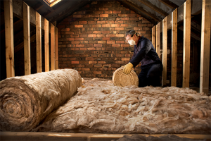 a man working on insulating a buildings attic