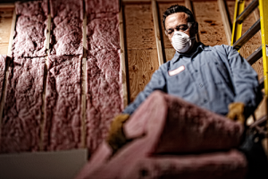 a workmen with mask installing insulation